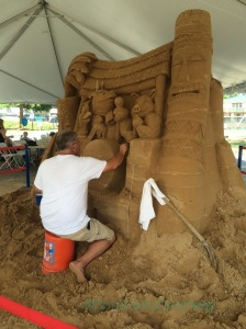 """Master sand sculptor Ted Siebert working on """"Pig and the Peaches."""""""