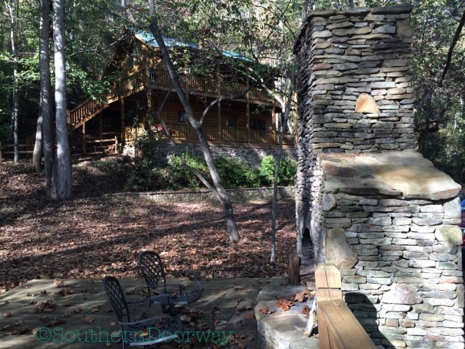 Photo of the cabin from deck on the river with fireplace.